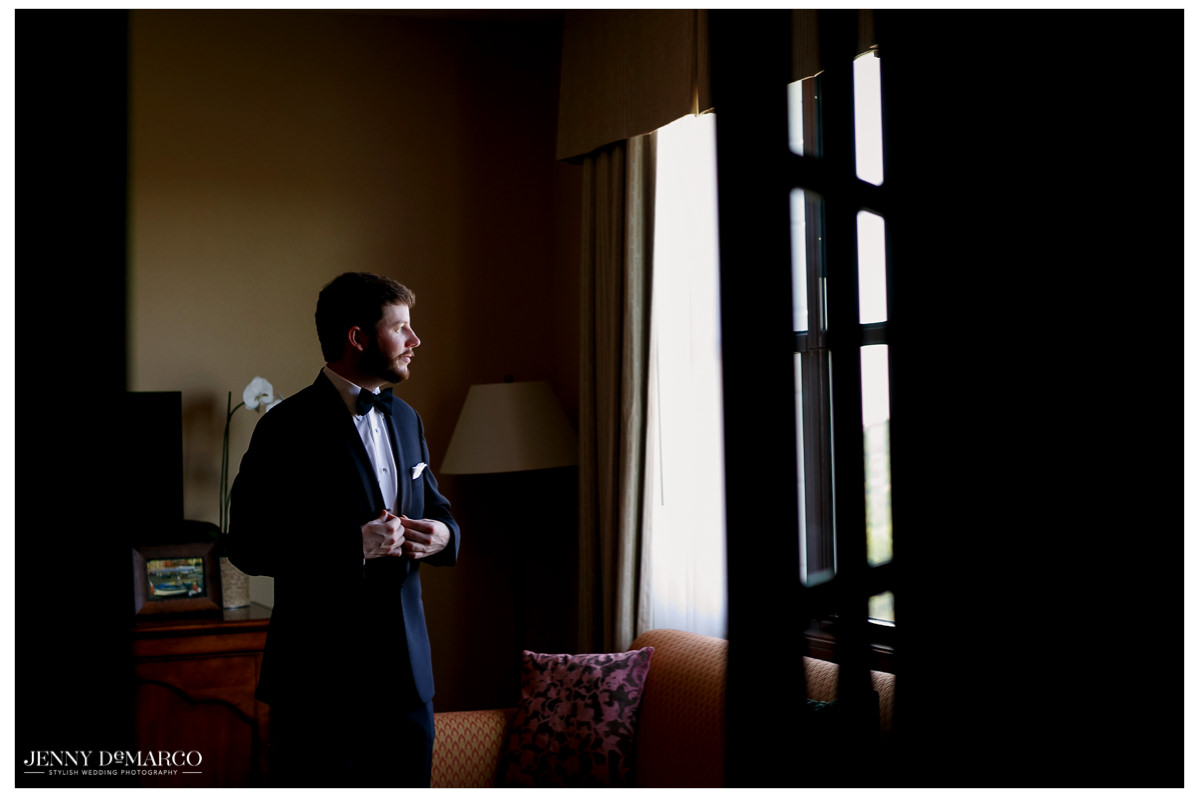 Groom looks longingly out the window waiting or the ceremony to begin.