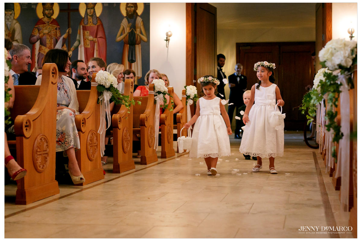 The flower girls throw petals all down the aisle.