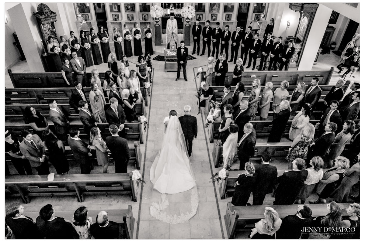 A wide angle shot of the bride ad her father walking down the aisle.