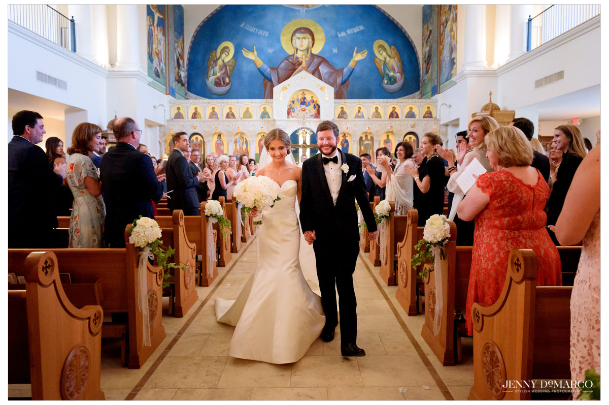 The couple walks down the aisle together as the crowd cheers for them.