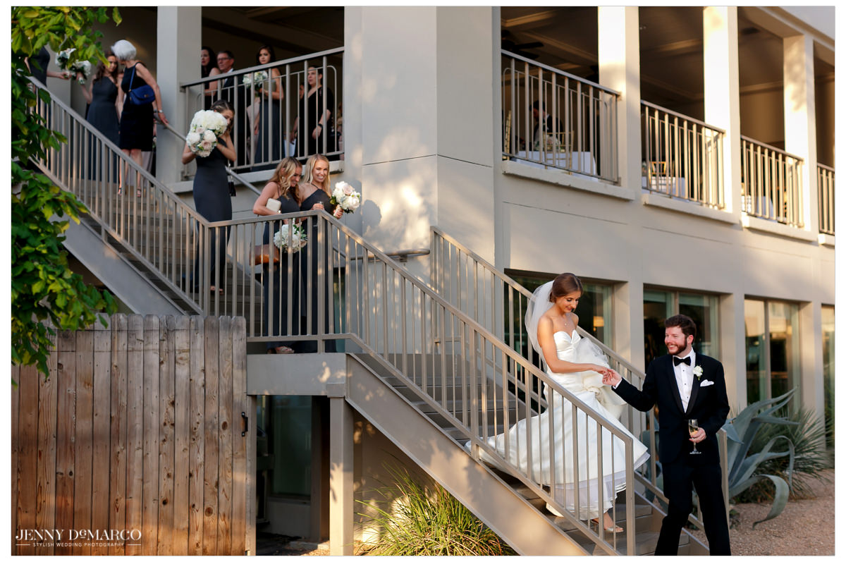 Groom helps his bride down the stairs towards the reception.