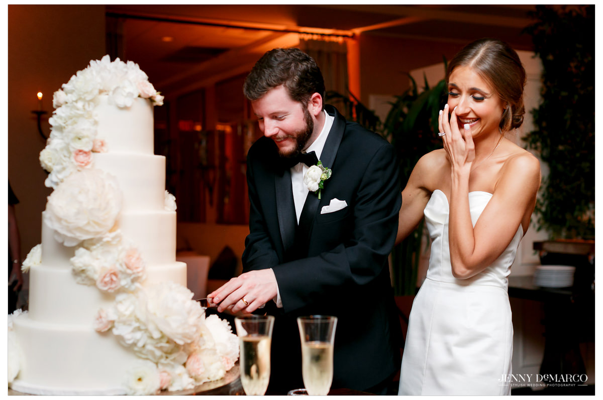 The couple cuts their floral wedding cake together.