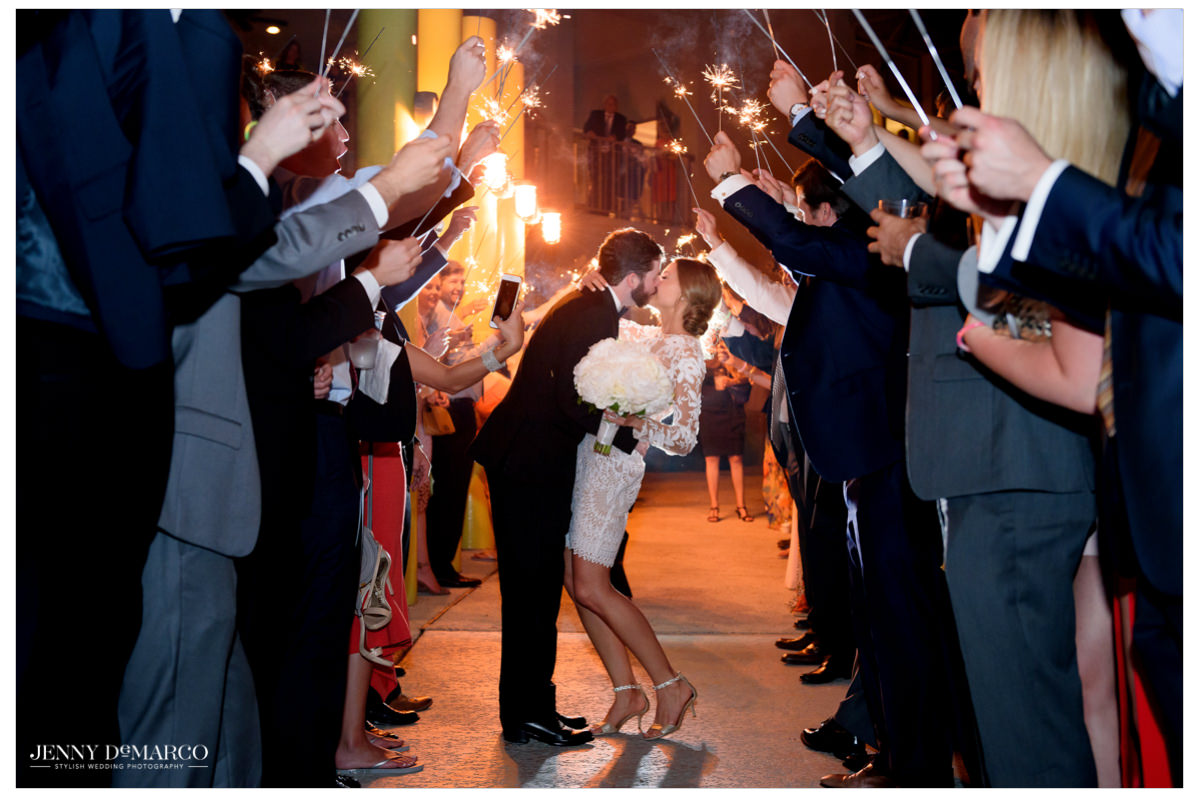 The couples shares one last final kiss of the night as guests use sparklers around them.