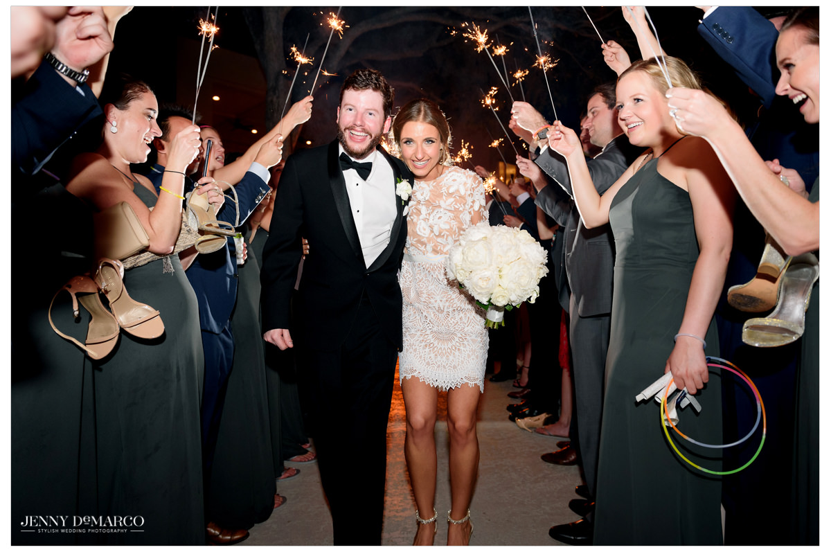 The couples walks through a line of sparklers held by guests.