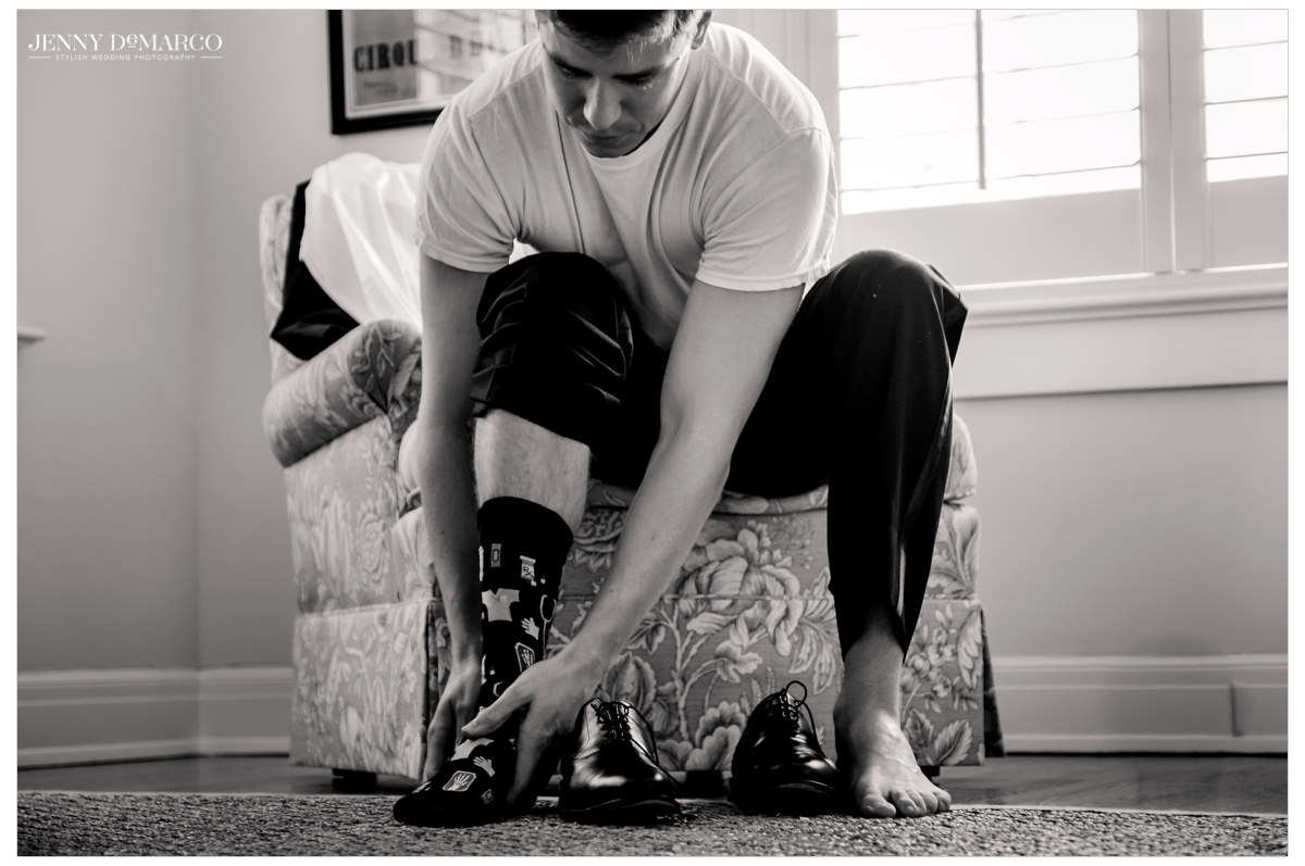 Groom puts his socks and shoes on.