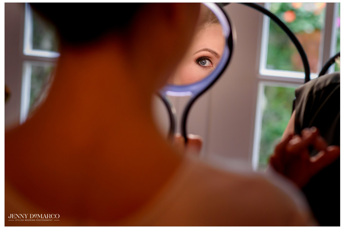 Bride looks at her makeup in the mirror.