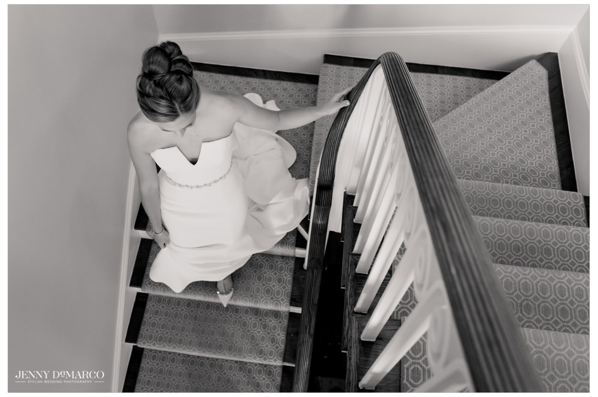 Bride descends the stairs in her full outfit.