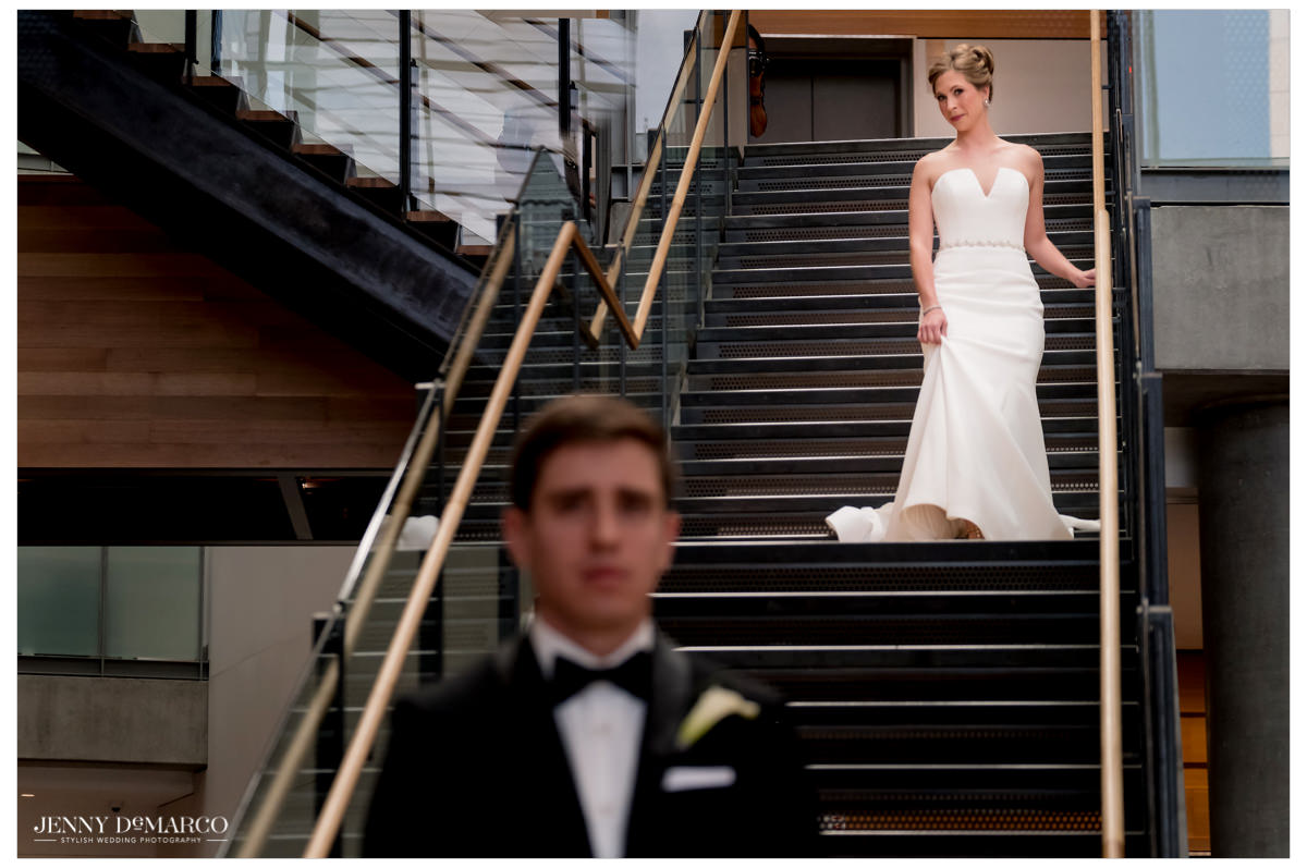 Bride walks down the stairs of the Austin Public Library for the first look.