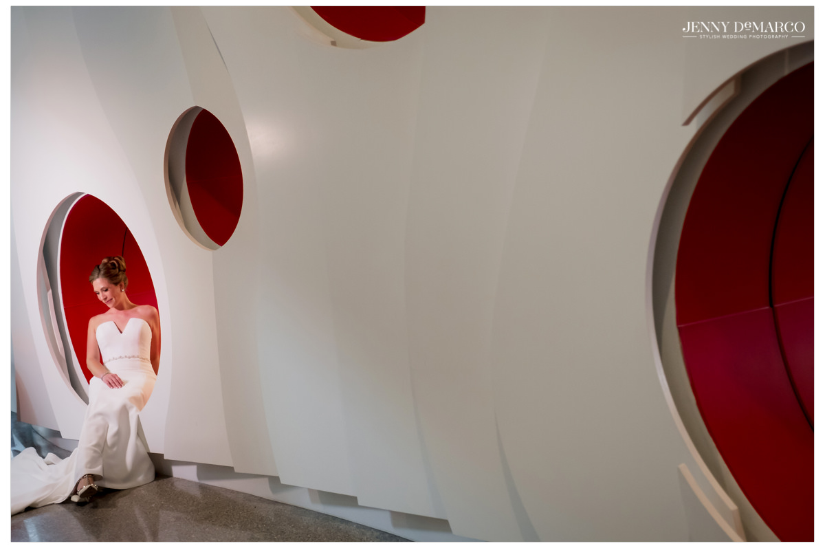 Bride poses in red modern wall circles.