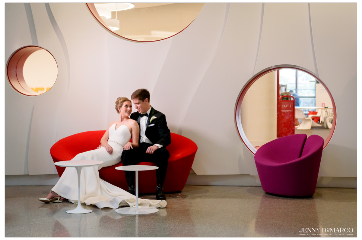 Bride and groom pose on a red couch.