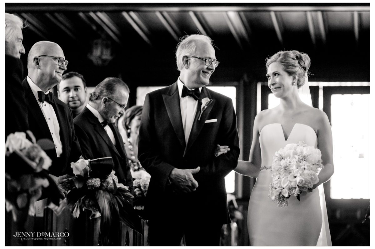 Bride looks at her father as they walk down.