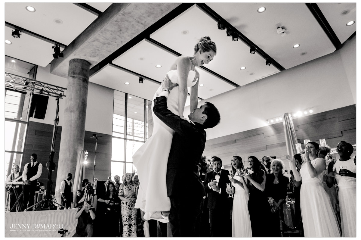 Grooms lifts his wife in the air.