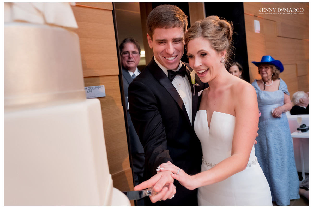 The couple cuts their white satin wedding cake.