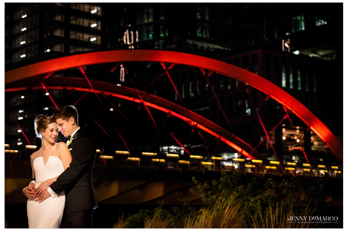 Intimate photo of the couple in front of a bridge.