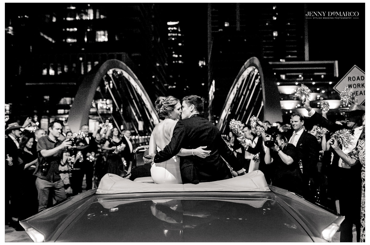 The couple kisses as they leave in a vintage car surrounded by their guests.