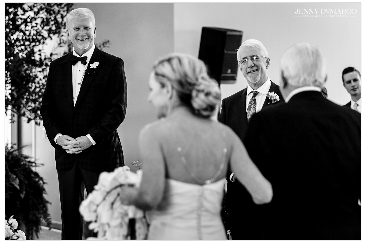 Kirsten walks down the aisle with her father towards her groom.