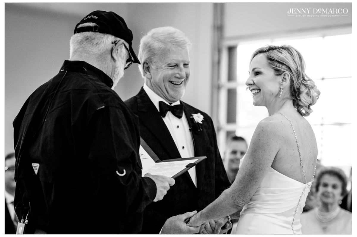 The older couple hold hands as the officiant officiates.