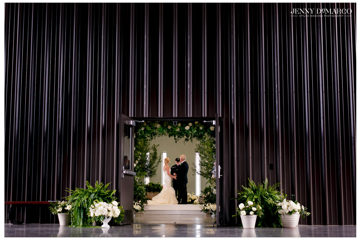 A wide angle shot of the older couple standing at the altar.