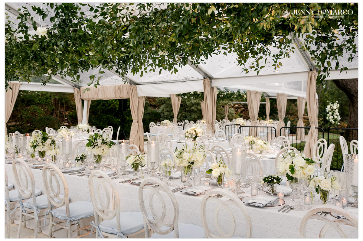 White round tables sit underneath a clear covered tent.
