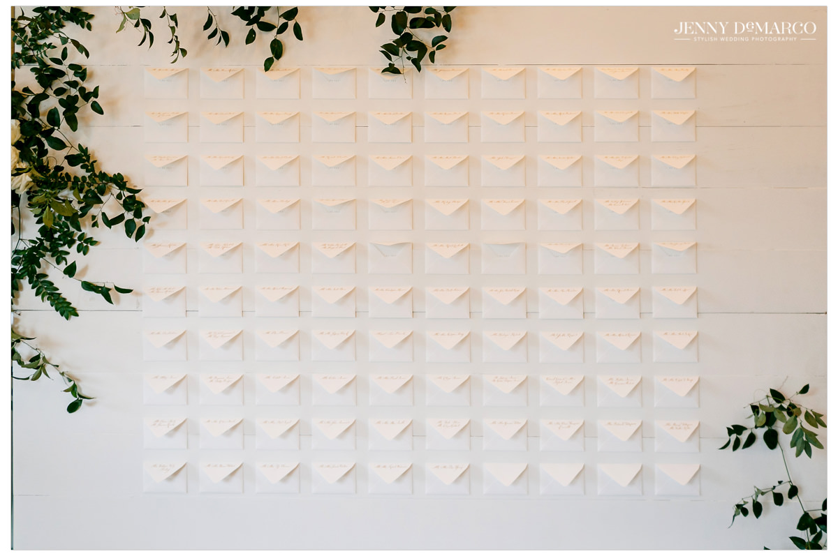 White envelopes line a wall telling guests where they are to sit.