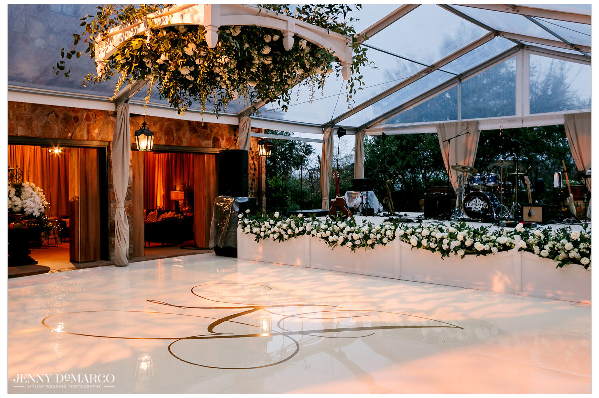 A white marble dance floor sits beneath greenery.