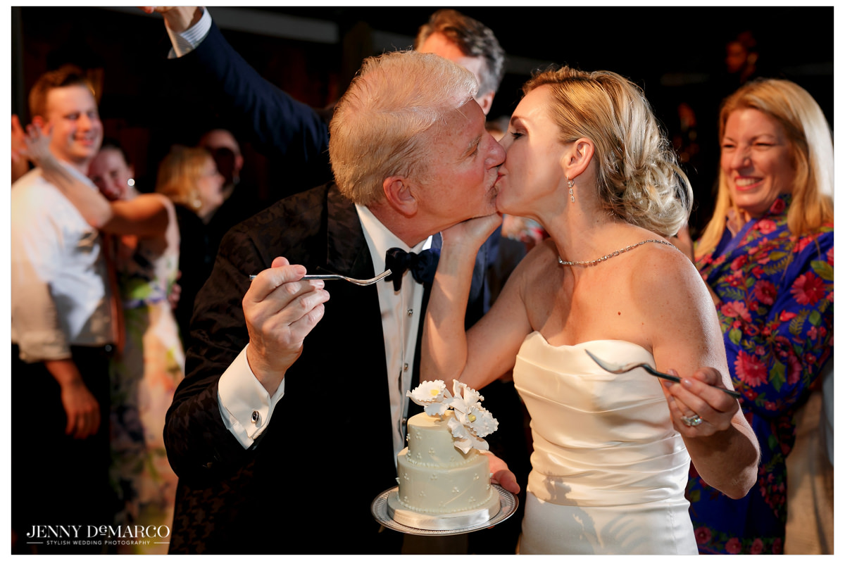The bride and groom share a kiss as they eat their satin wedding cake.
