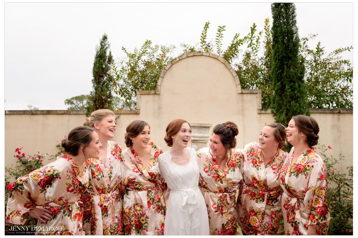 Bridesmaids smile with the bride before they get ready.