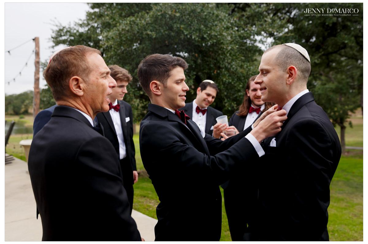 Groomsmen help put on the groom's tie.