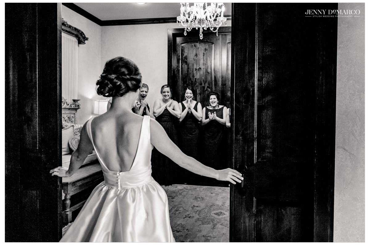 The bride shows off her look to her bridesmaids.