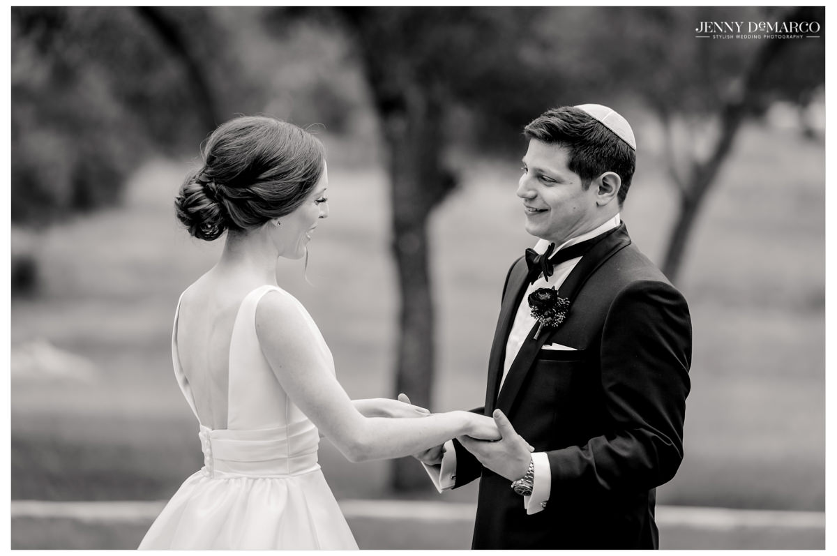 The groom holds his bride's hands.