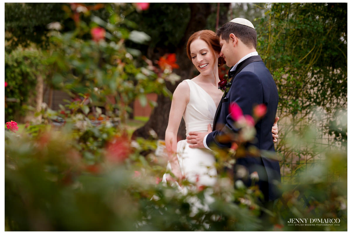 The couple embraces in a garden.
