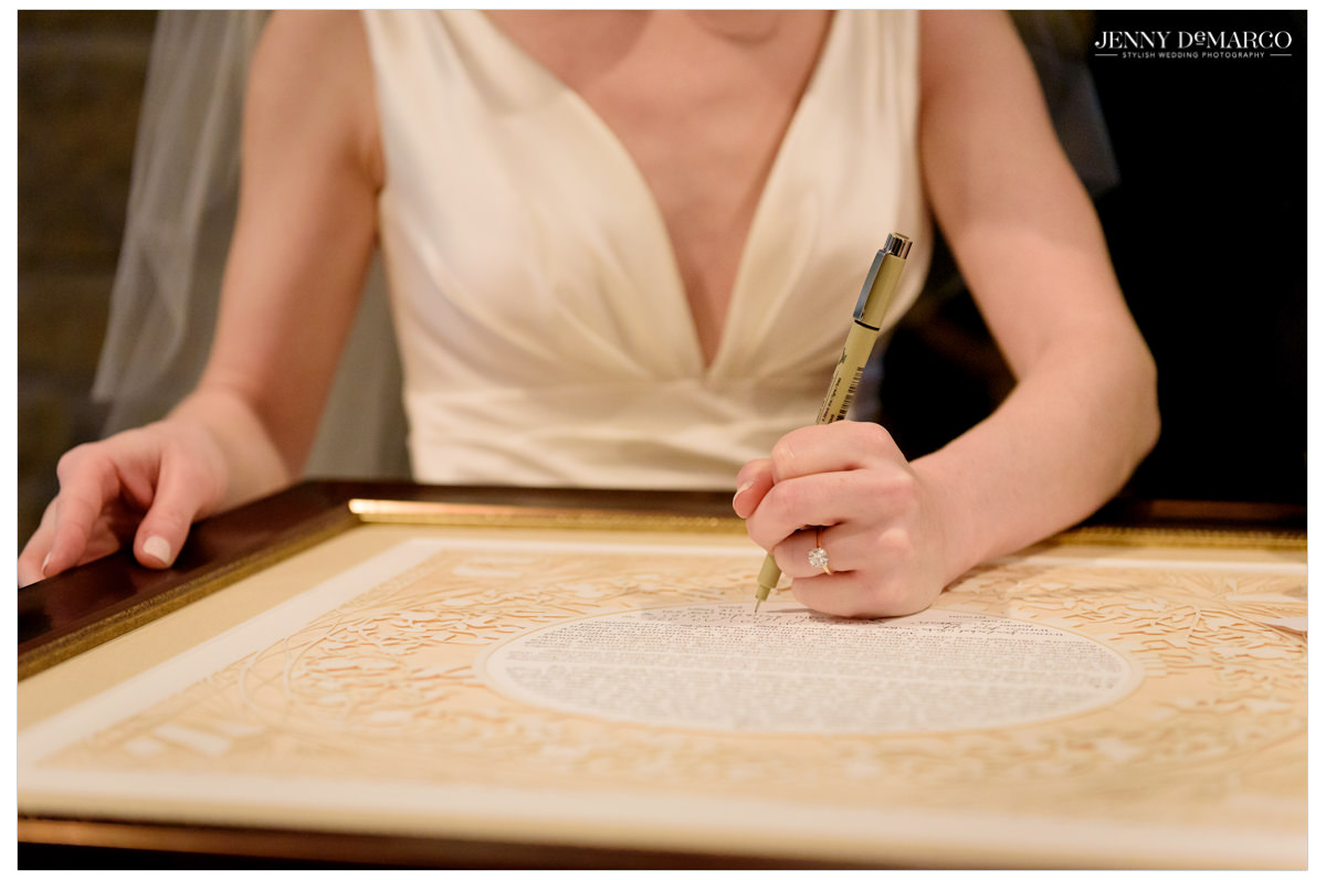 Bride signs the marriage license.
