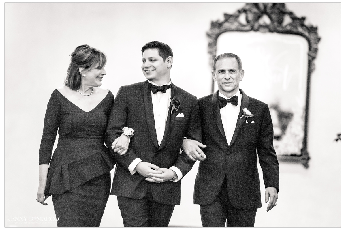 Groom is walked down the aisle by his parents.