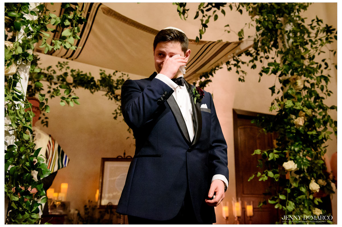 Groom sheds a tear as he looks at his bride.