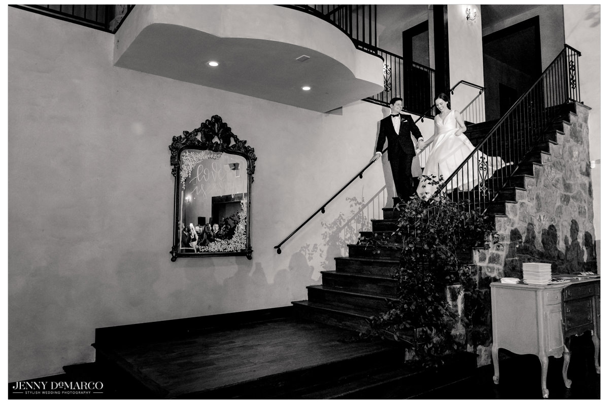 Bride and groom walk down stairs towards the reception.