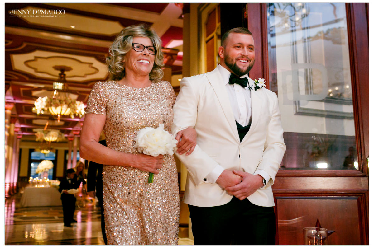 Groom is walked down the aisle by his mom.