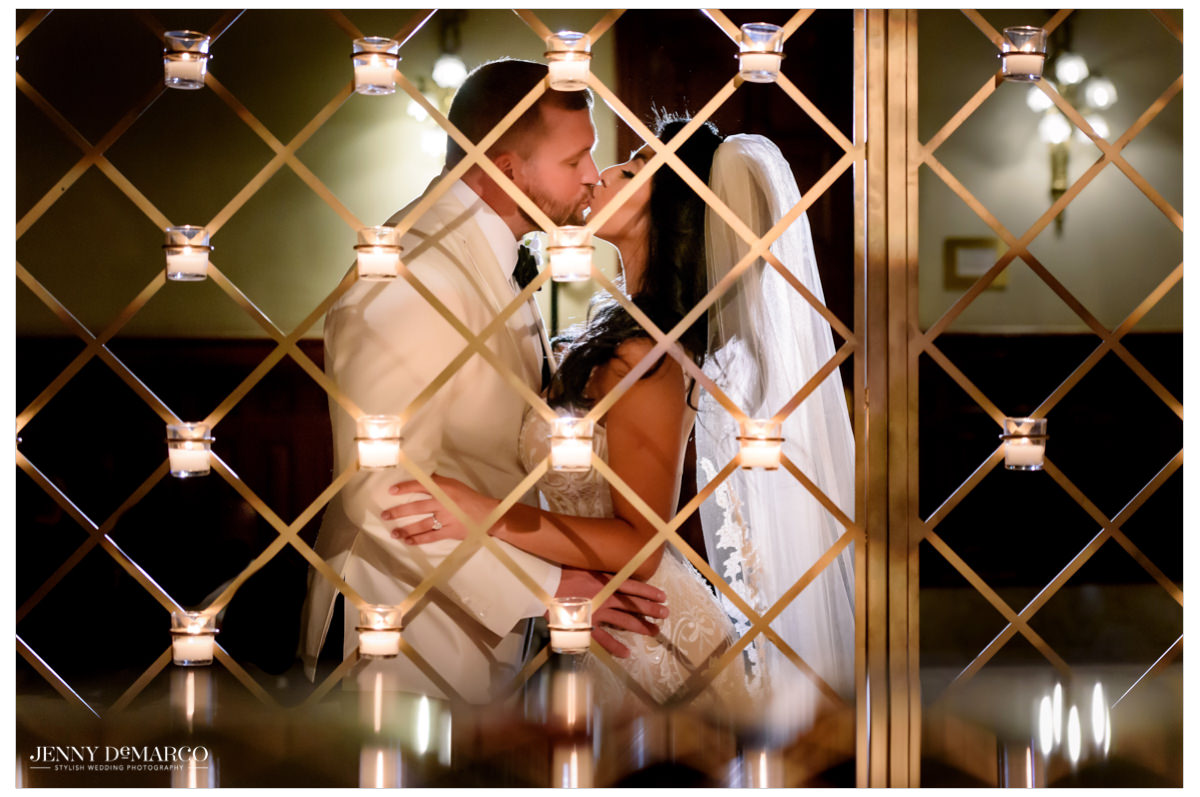 The couple kisses in the candlelight.