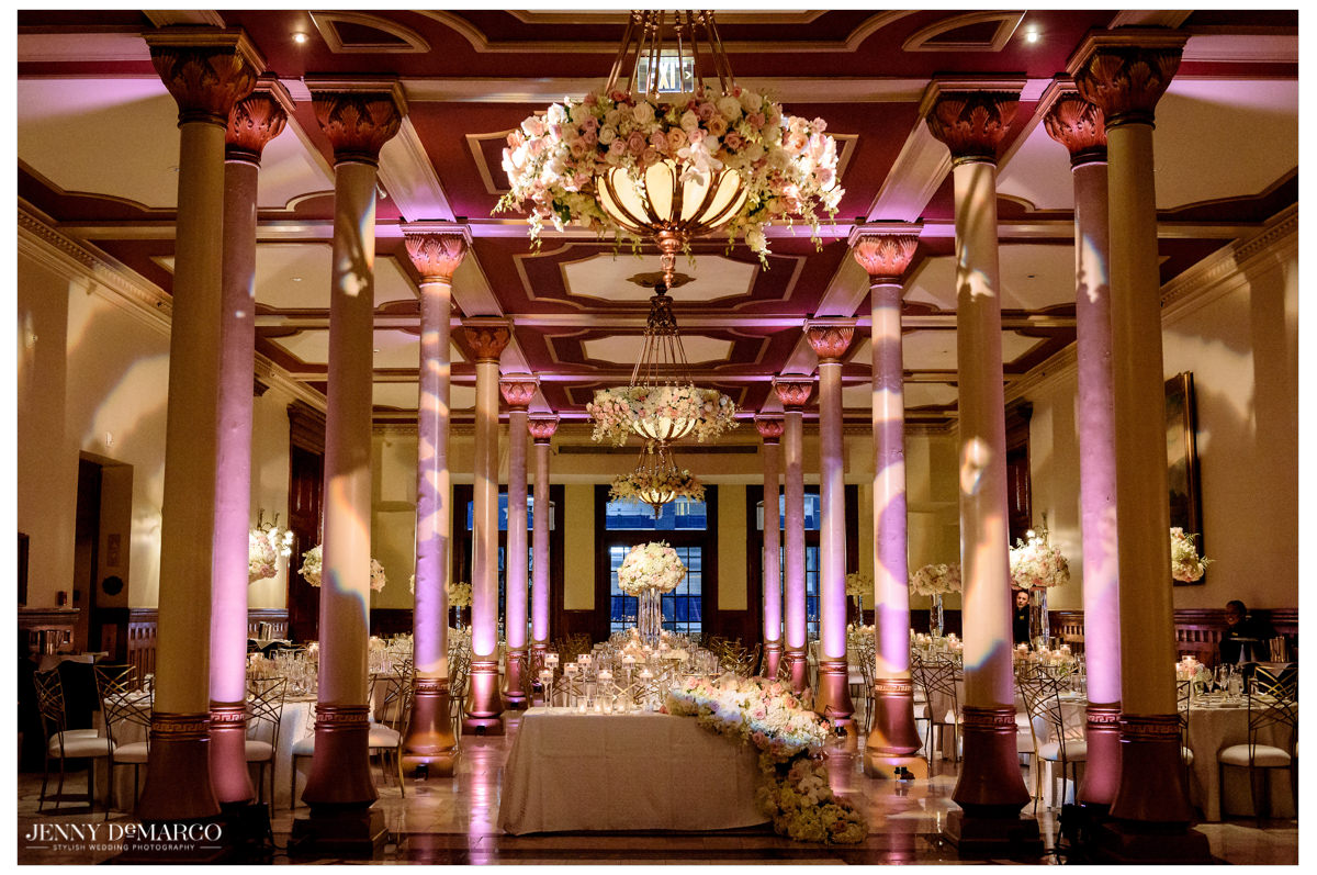 The reception is decorated with white and pink florals and gold accents.