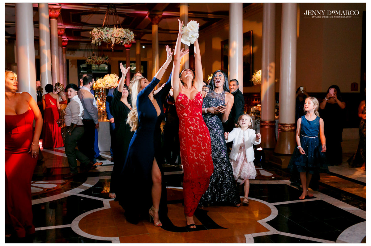 A guest catches her bouquet.