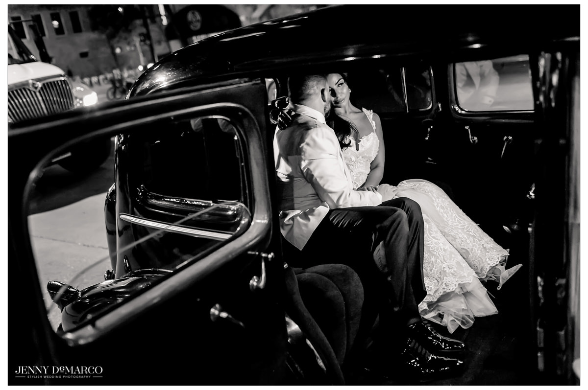 A romantic black and white photo of the couple in their exit car.