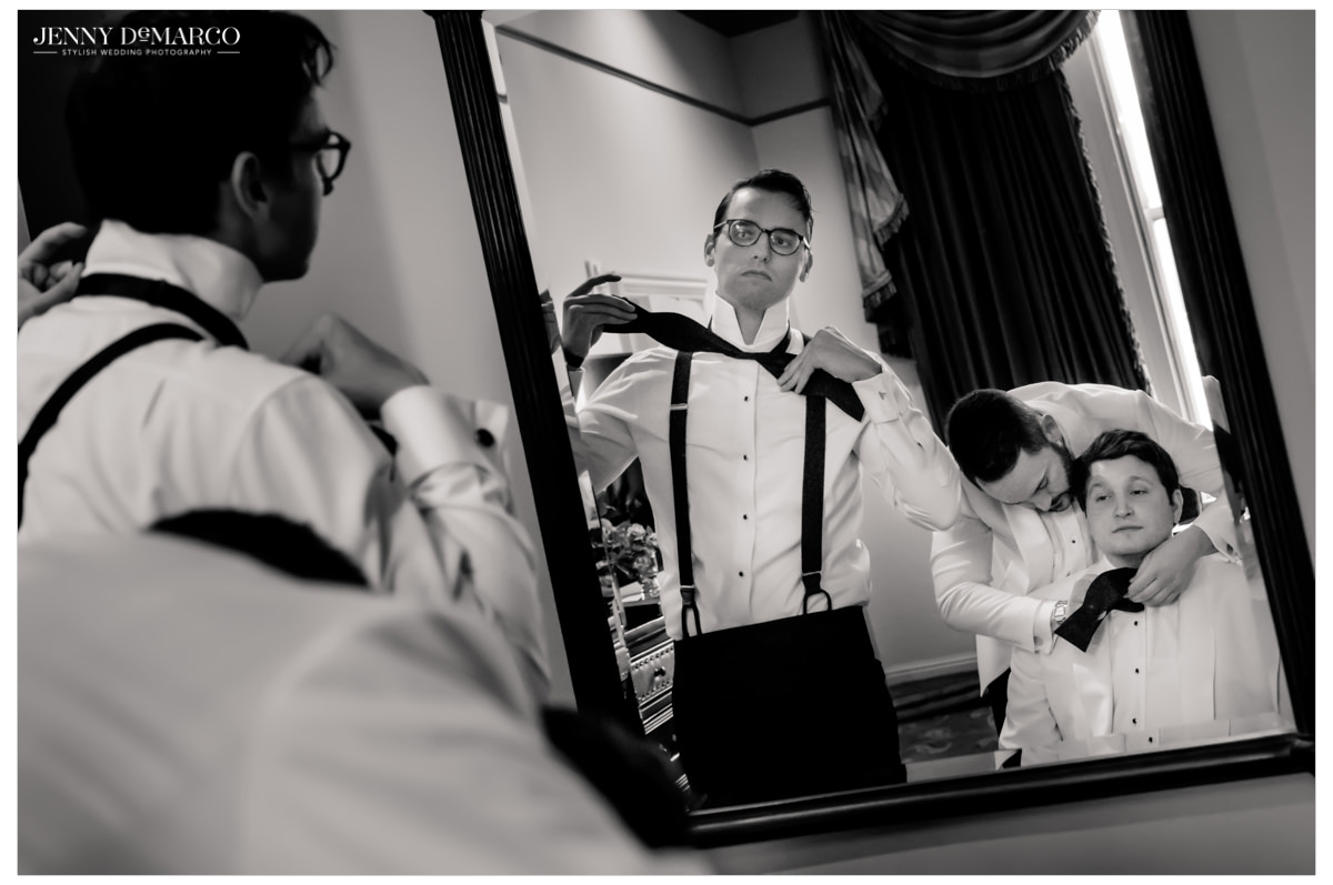Groomsmen help each other with ties.