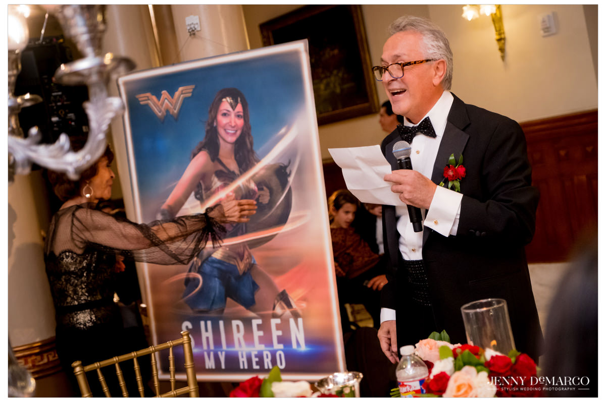 Father presents the couple with a poster with the bride dressed as Wonder Woman.