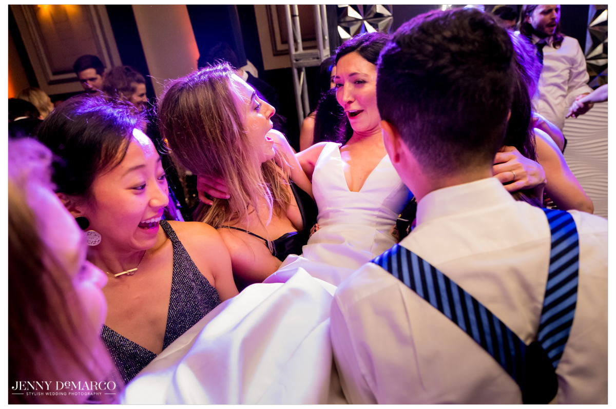 Bride is lifted in the air by her friends.