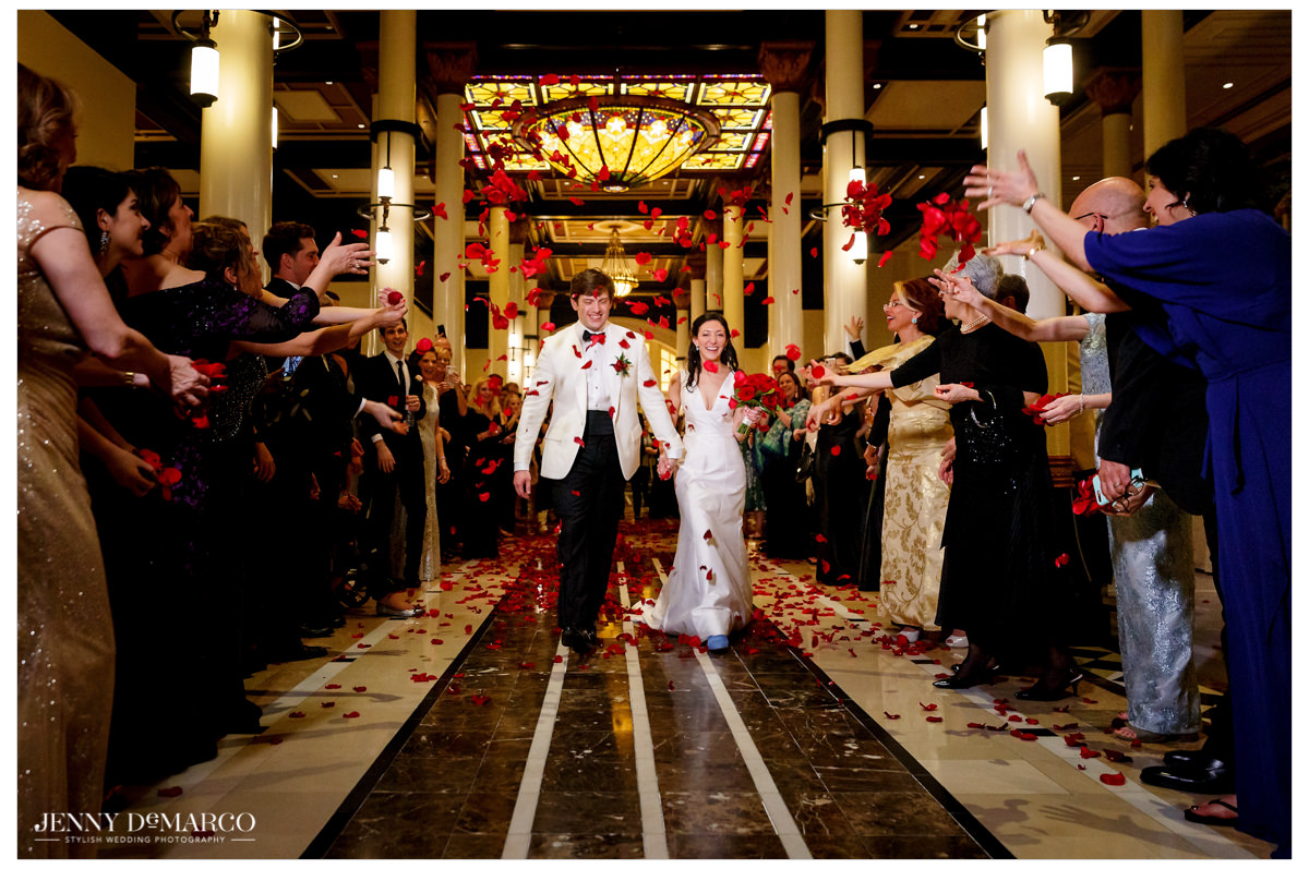 Bride and Groom exit the Driskill with red flowers thrown at them.