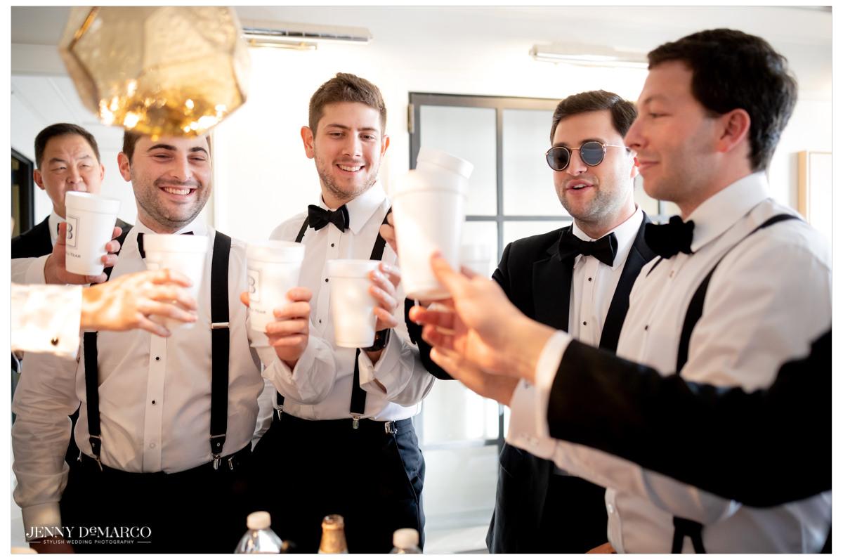 Groomsmen cheers drinks.