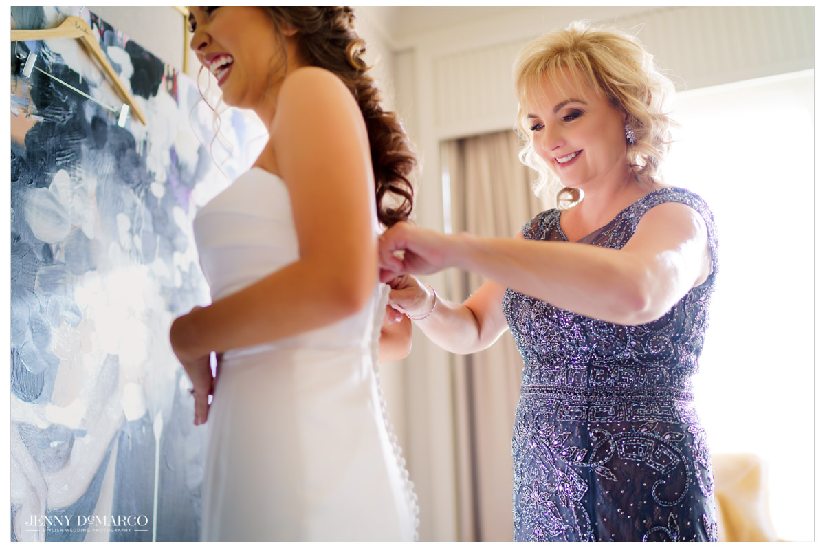 Bride gets help putting on her wedding gown.