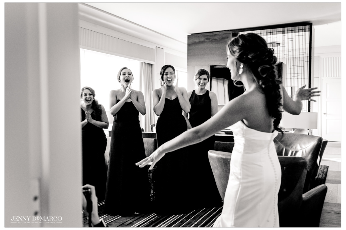 Bride shows off her look to her bridesmaids.