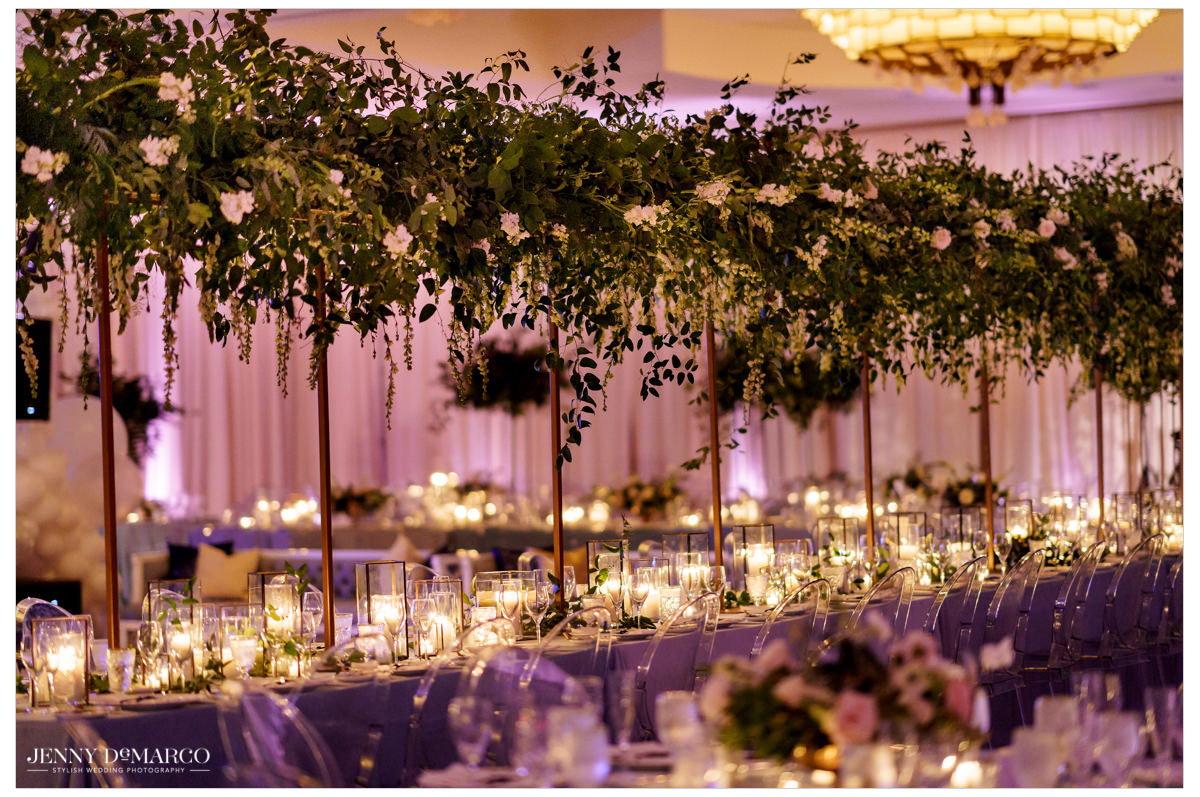Greenery lines the long candlelit tables.