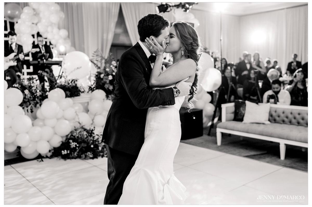 Bride and groom kiss on the dancefloor.