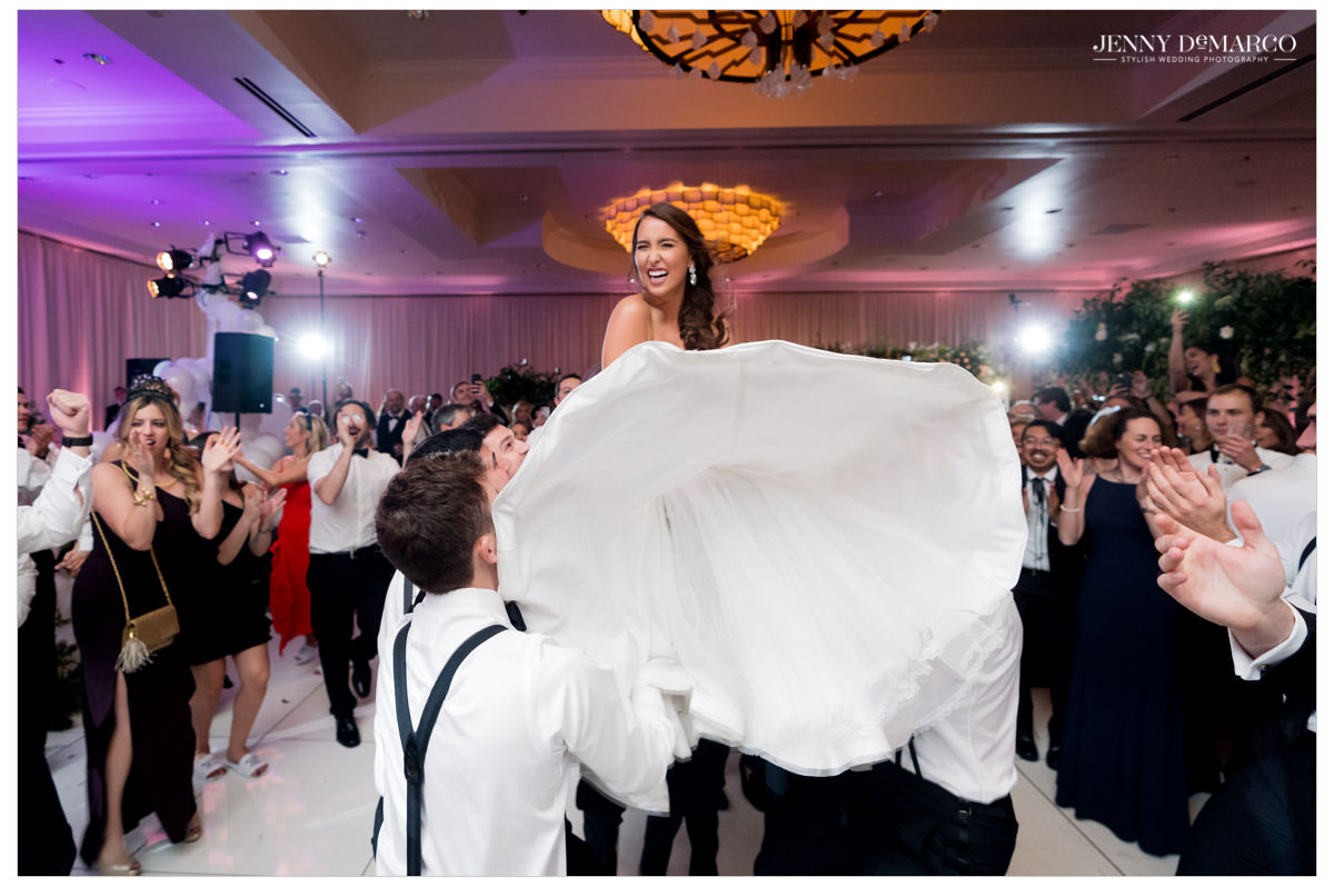 Bride is lifted high in the air on a chair.